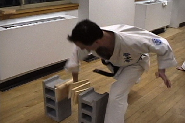 A karate classmate breaks three boards without spacers.